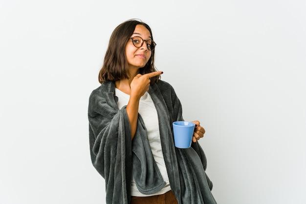 Jeune femme latine avec couverture isolée sur un mur blanc souriant joyeusement pointant avec l'index loin.
