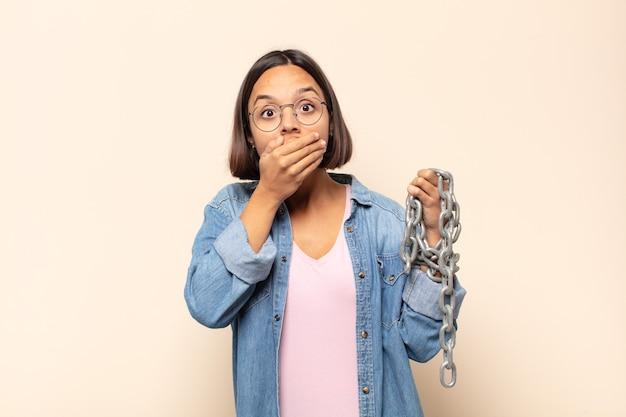 Jeune femme latine couvrant la bouche avec les mains avec une expression choquée et surprise, en gardant un secret ou en disant oups