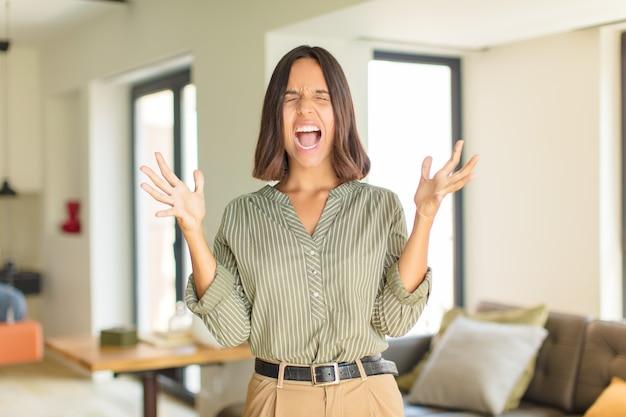 Jeune femme latine hurlant furieusement, se sentant stressée et agacée avec les mains en l'air en disant pourquoi moi