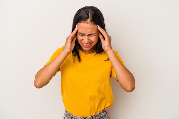 Jeune femme latine isolée sur fond blanc ayant mal à la tête, touchant le devant du visage.