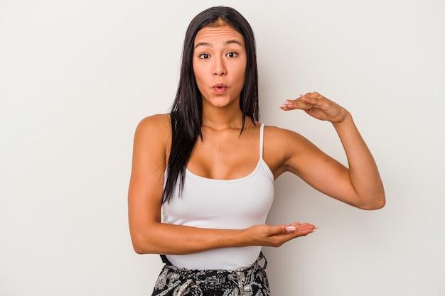 Jeune femme latine isolée sur fond blanc choquée et étonnée tenant un espace de copie entre les mains.