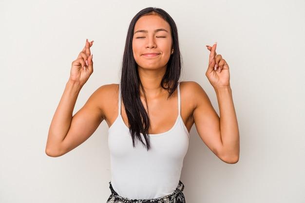 Jeune femme latine isolée sur fond blanc croisant les doigts pour avoir de la chance
