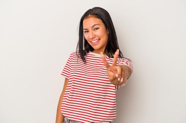 Jeune femme latine isolée sur fond blanc montrant le signe de la victoire et souriant largement.