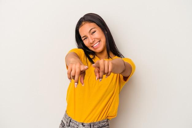Jeune femme latine isolée sur fond blanc pointant vers l'avant avec les doigts.