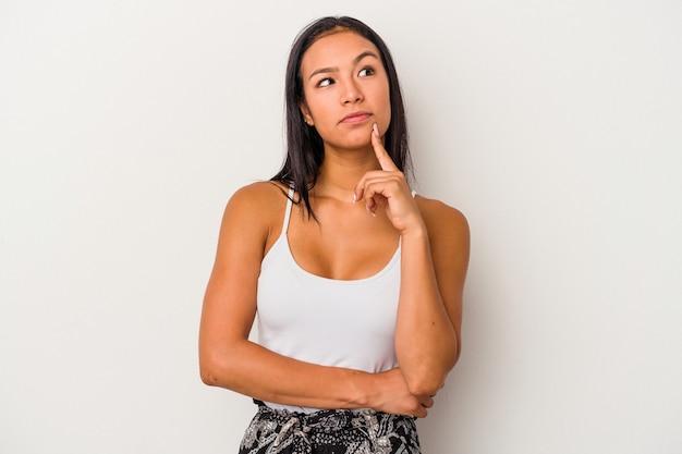Jeune femme latine isolée sur fond blanc regardant de côté avec une expression douteuse et sceptique.