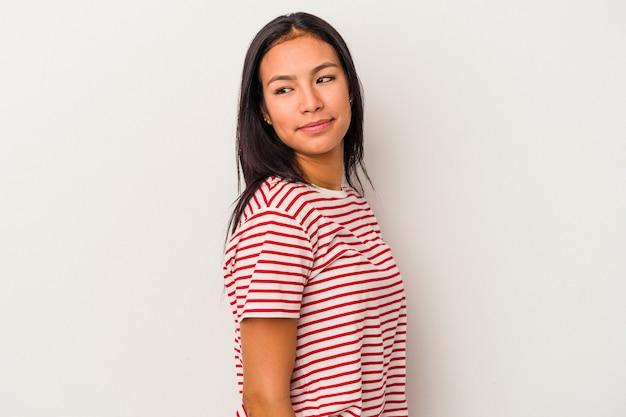 Jeune femme latine isolée sur fond blanc regarde de côté souriante, gaie et agréable.