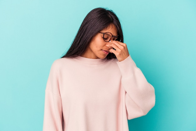 Jeune femme latine isolée sur fond bleu ayant mal à la tête, touchant le devant du visage.