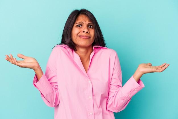 Jeune femme latine isolée sur fond bleu doutant et haussant les épaules dans un geste de questionnement.