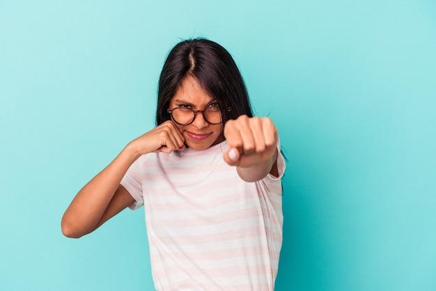 Jeune femme latine isolée sur fond bleu jetant un coup de poing, colère, combat à cause d'une dispute, boxe.