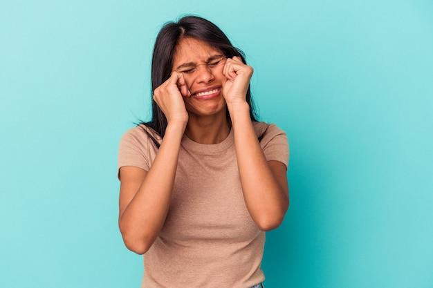 Jeune femme latine isolée sur fond bleu pleurnichant et pleurant de manière inconsolable.