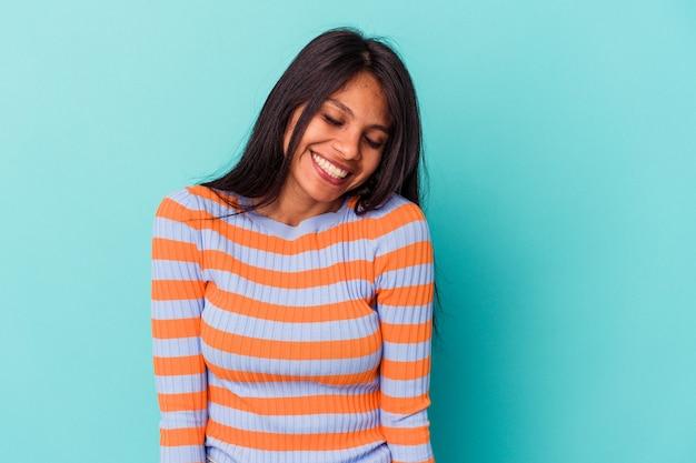 Jeune femme latine isolée sur fond bleu rit et ferme les yeux, se sent détendue et heureuse.