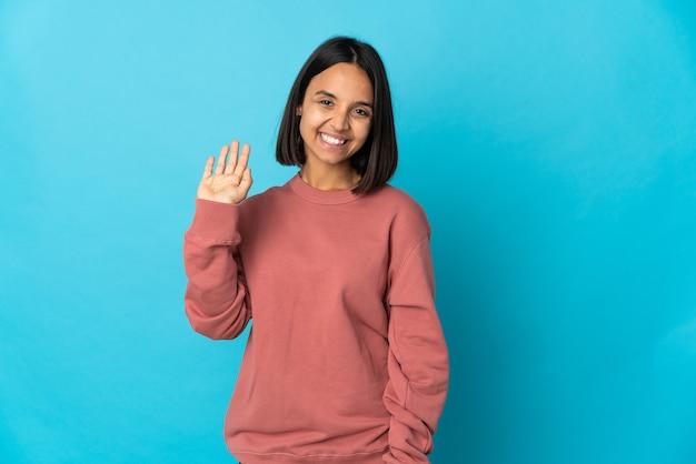 Jeune femme latine isolée sur fond bleu saluant avec la main avec une expression heureuse