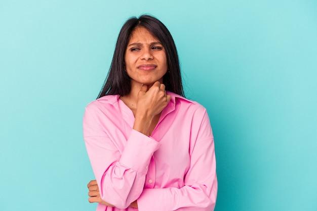 Une jeune femme latine isolée sur fond bleu souffre de douleurs dans la gorge à cause d'un virus ou d'une infection.