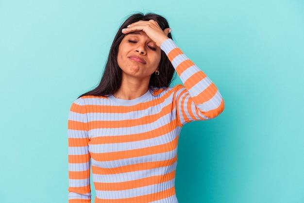 Jeune femme latine isolée sur fond bleu touchant les tempes et ayant des maux de tête.
