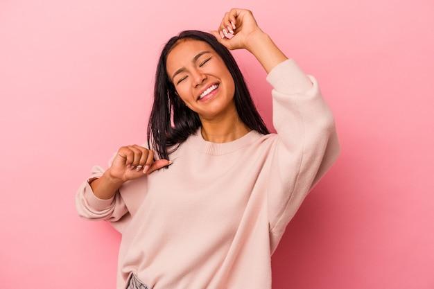 Jeune femme latine isolée sur fond rose célébrant une journée spéciale, saute et lève les bras avec énergie.