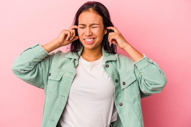 Jeune femme latine isolée sur fond rose couvrant les oreilles avec les doigts, stressée et désespérée par une ambiance bruyante.