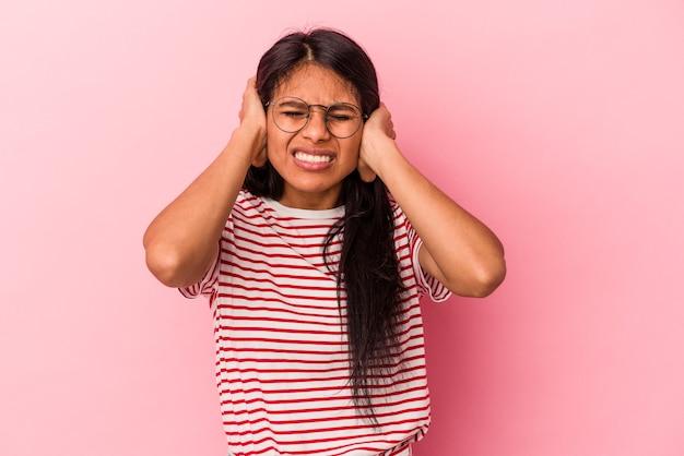 Jeune femme latine isolée sur fond rose couvrant les oreilles avec les mains.