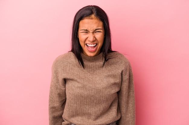 Jeune femme latine isolée sur fond rose criant très en colère, concept de rage, frustré.