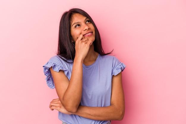 Jeune femme latine isolée sur fond rose détendue en pensant à quelque chose en regardant un espace de copie.