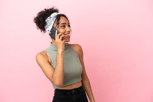 Jeune femme latine isolée sur fond rose gardant une conversation avec le téléphone portable