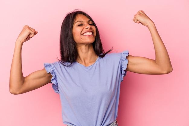 Jeune femme latine isolée sur fond rose levant le poing après une victoire, concept gagnant.