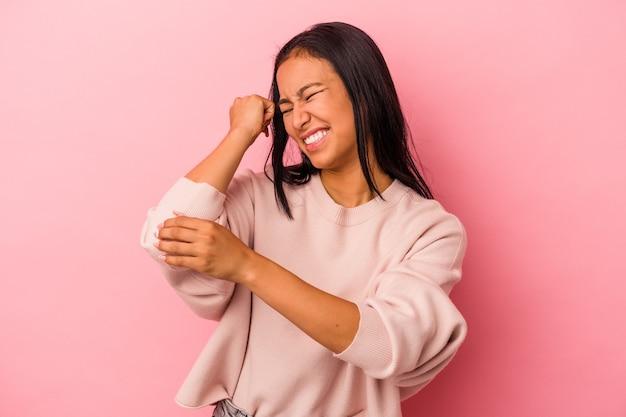 Jeune femme latine isolée sur fond rose massant le coude, souffrant après un mauvais mouvement.