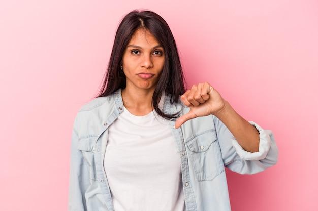 Jeune femme latine isolée sur fond rose montrant un geste d'aversion, les pouces vers le bas. notion de désaccord.