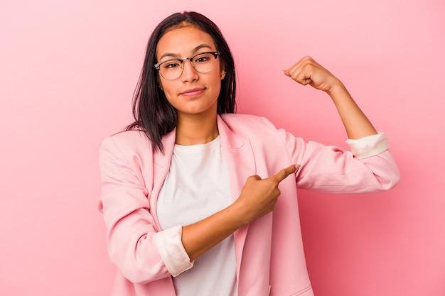 Jeune femme latine isolée sur fond rose montrant un geste de force avec les bras, symbole du pouvoir féminin