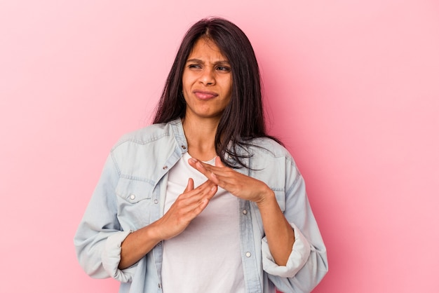 Jeune femme latine isolée sur fond rose montrant un geste de temporisation.