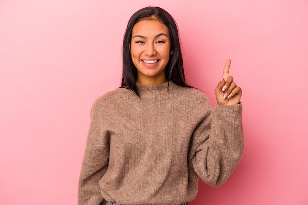 Jeune femme latine isolée sur fond rose montrant le numéro un avec le doigt.