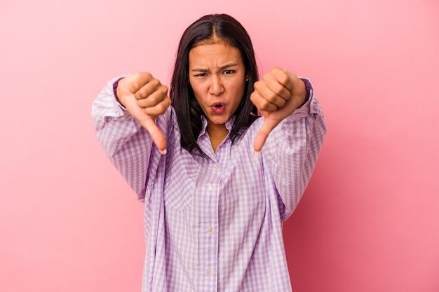 Jeune femme latine isolée sur fond rose montrant le pouce vers le bas et exprimant son aversion.
