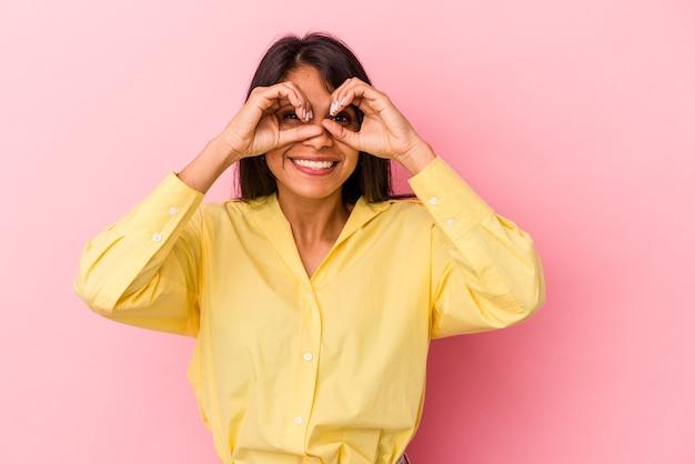 Jeune femme latine isolée sur fond rose montrant un signe d'accord sur les yeux