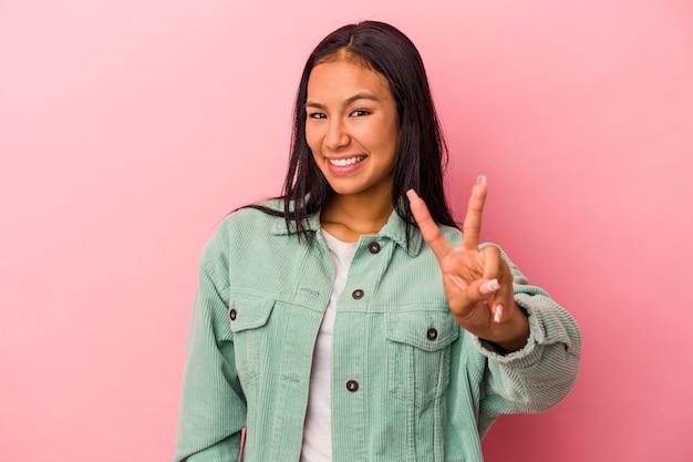 Jeune femme latine isolée sur fond rose montrant le signe de la victoire et souriant largement.