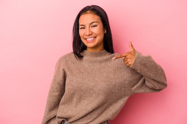 Jeune femme latine isolée sur fond rose personne pointant à la main vers un espace de copie de chemise, fière et confiante
