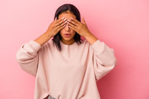 Jeune femme latine isolée sur fond rose peur couvrant les yeux avec les mains.
