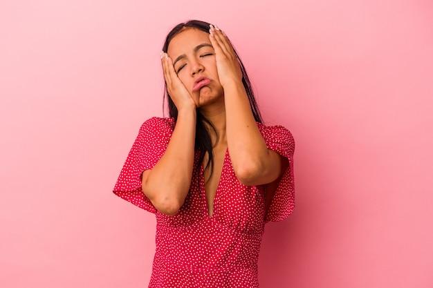 Jeune femme latine isolée sur fond rose pleurnichant et pleurant de manière inconsolable.
