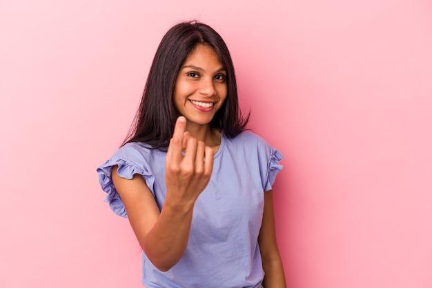 Jeune femme latine isolée sur fond rose pointant du doigt vers vous comme si vous vous invitiez à vous rapprocher.