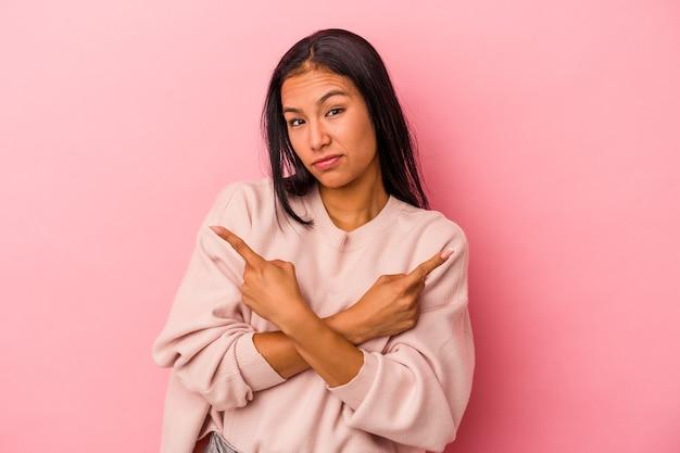 Une jeune femme latine isolée sur fond rose pointe sur le côté, essaie de choisir entre deux options.