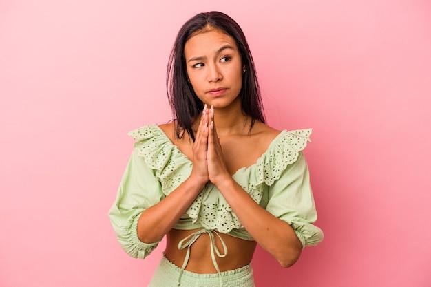 Jeune femme latine isolée sur fond rose priant, montrant sa dévotion, personne religieuse à la recherche d'une inspiration divine.
