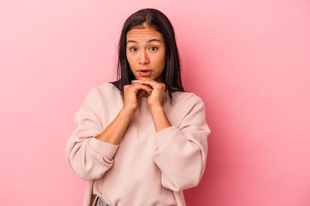 Jeune femme latine isolée sur fond rose priant pour la chance, étonnée et ouvrant la bouche regardant vers l'avant.