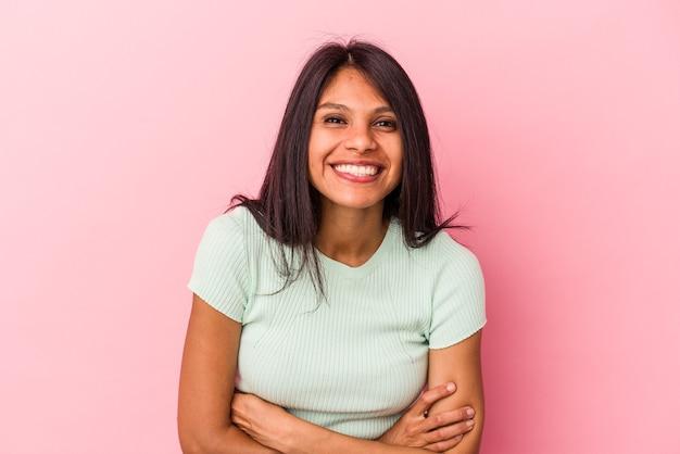Jeune femme latine isolée sur fond rose en riant et en s'amusant.