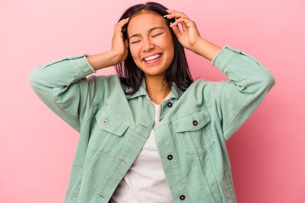 Jeune femme latine isolée sur fond rose rit joyeusement en gardant les mains sur la tête. notion de bonheur.