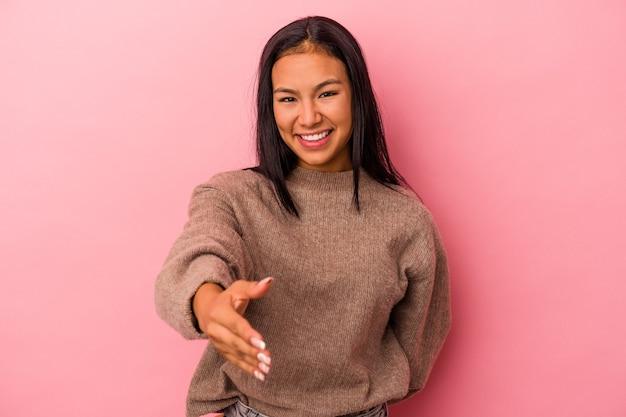 Jeune femme latine isolée sur fond rose s'étendant la main à la caméra en geste de salutation.
