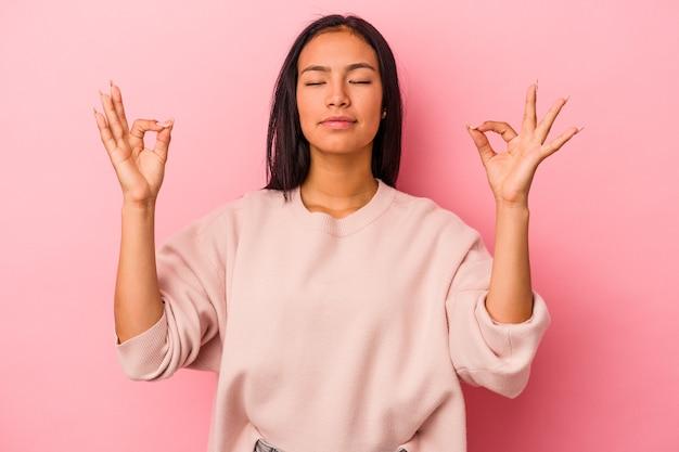 Jeune femme latine isolée sur fond rose se détend après une dure journée de travail, elle fait du yoga.