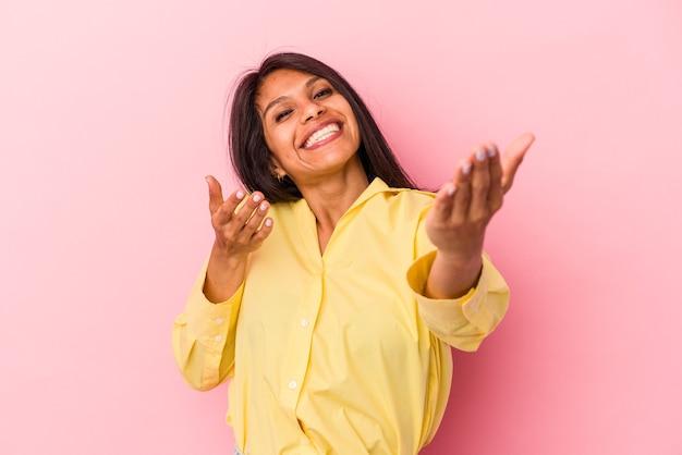 Jeune femme latine isolée sur fond rose se sent confiante en donnant un câlin à la caméra.