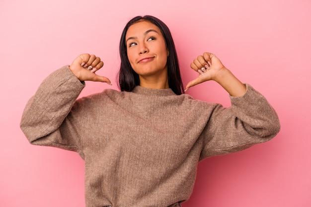 Jeune femme latine isolée sur fond rose se sent fière et confiante, exemple à suivre.