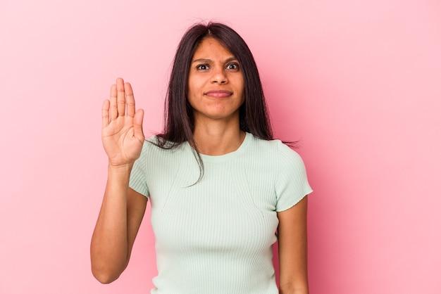 Jeune femme latine isolée sur fond rose souriante joyeuse montrant le numéro cinq avec les doigts.