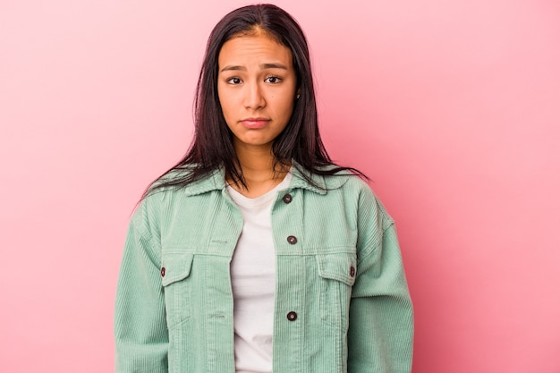 Jeune femme latine isolée sur fond rose, visage triste et sérieux, se sentant misérable et mécontent.