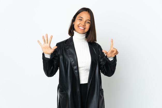 Jeune femme latine isolée sur un mur blanc comptant sept avec les doigts