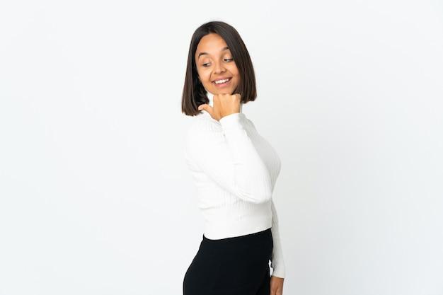 Jeune femme latine isolée sur un mur blanc pointant vers le côté pour présenter un produit
